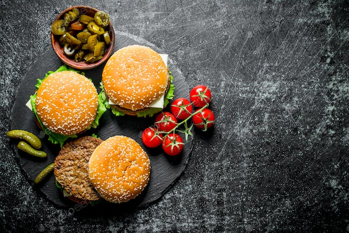 Burgers with tomatoes and gherkins on a stone Board.