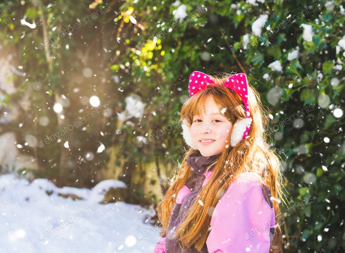 Portrait of redhead girl in winter snow forest