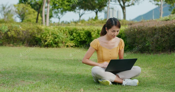 Woman work on laptop computer and sit on green lawn