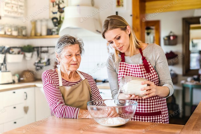 An elderly grandmother with an adult granddaughter at home, baking.