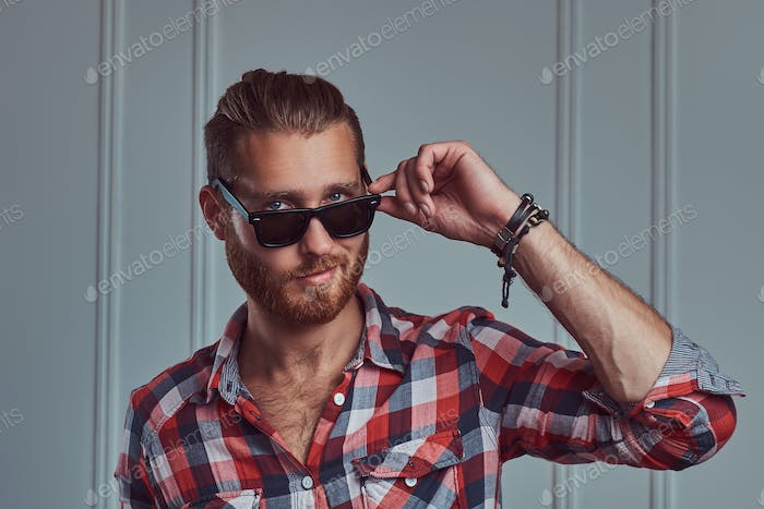 Handsome stylish redhead man in a flannel shirt and sunglasses, posing in a studio