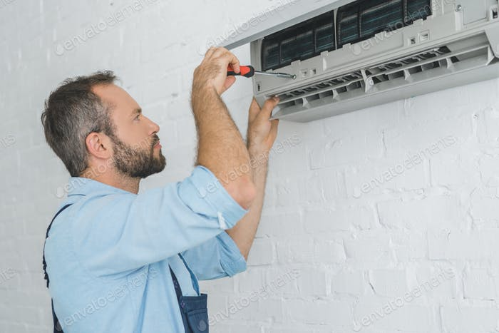 repairman fixing air conditioner with screwdriver at summer heat