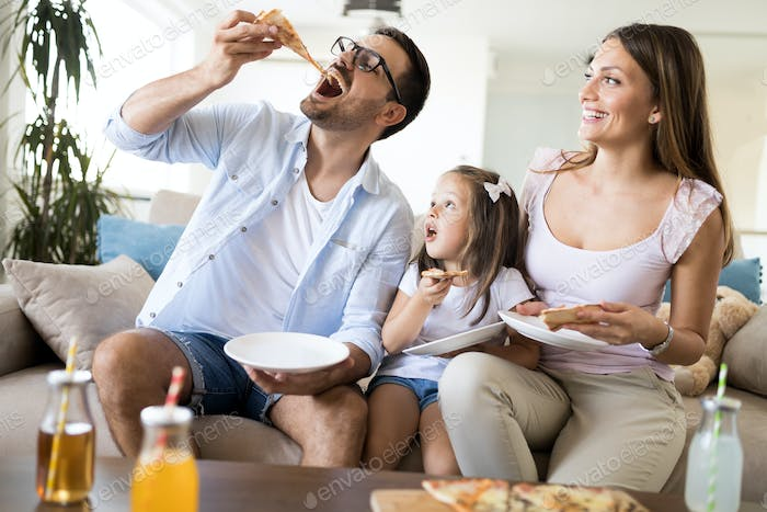 Portrait of happy family sharing pizza at home