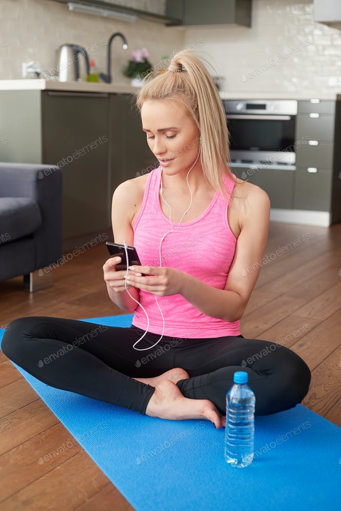 Cute woman sitting on yoga mat and browsing mobile phone for songs