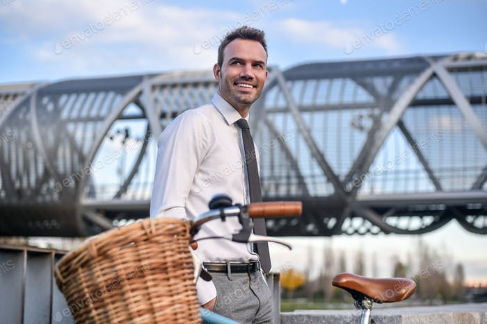 Business man with vintage bicycle by the river