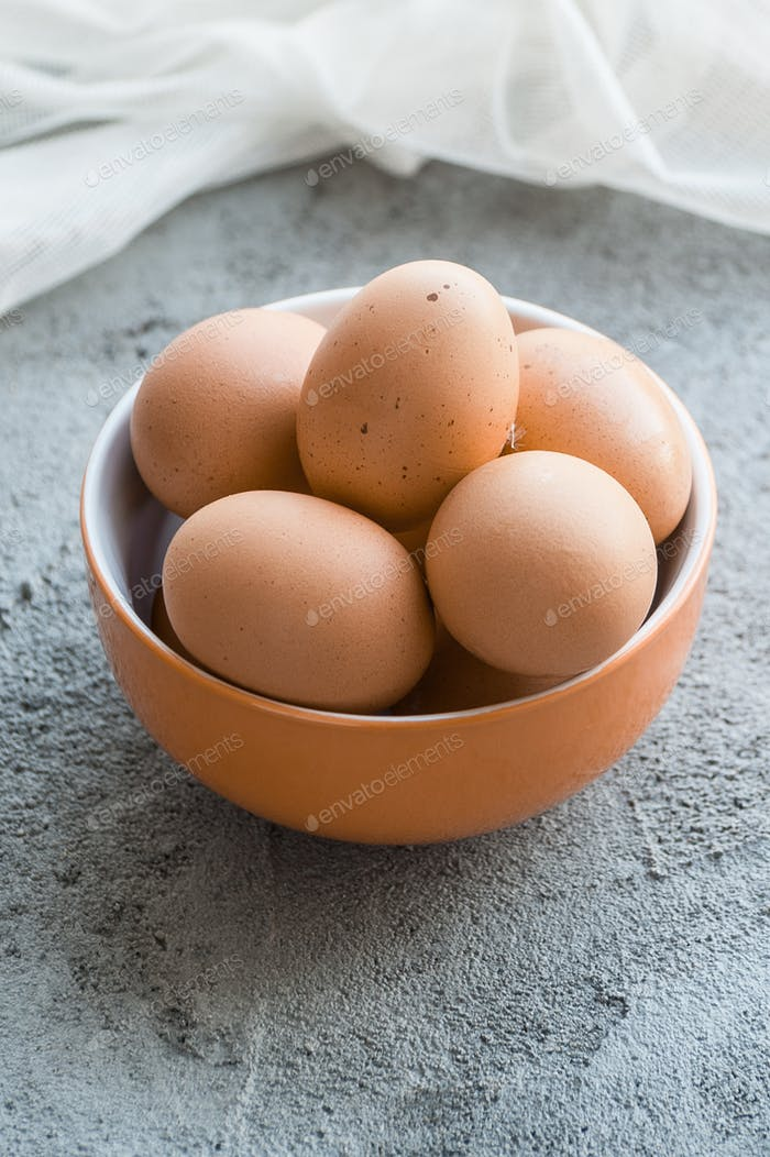 Brown chicken eggs in a bowl on a gray stone table.