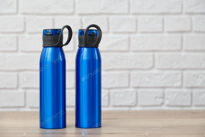 Two blue metal thermoses. Standing on wooden table with white brick background