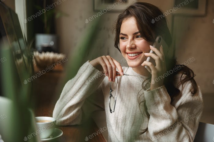 Image of young beautiful caucasian woman talking on smartphone in cafe