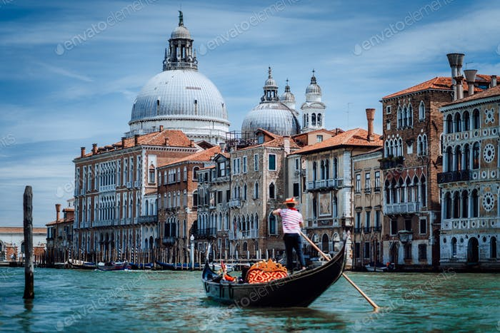 Traditional Gondola and gondolier on Canal Grande with Basilica di Santa Maria della Salute in the