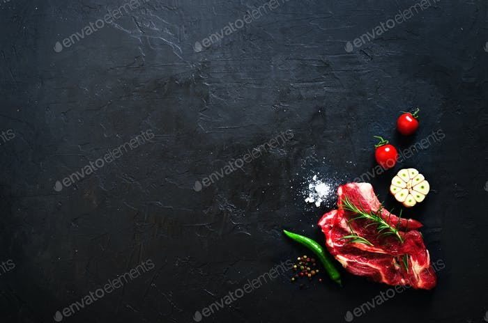 Raw meat, beef steak on a stone cutting board with rosemary, spices, salt, oil, cherry tomatoes, hot
