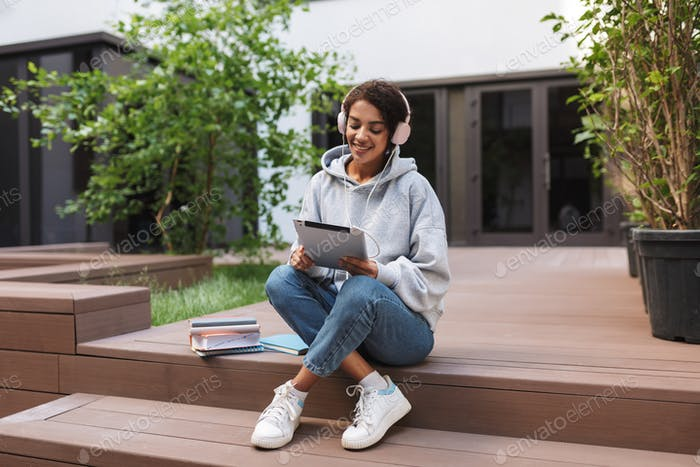 Beautiful smiling lady sitting in headphones and tablet in hands