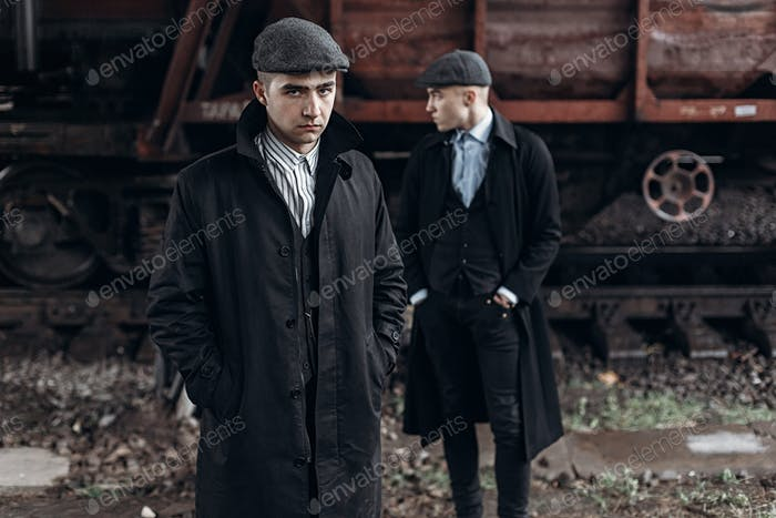 Stylish gangsters men, posing on background of railway