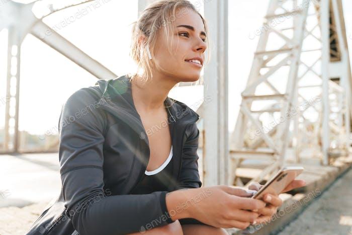 Beautiful young sportsgirl sitting on a bridge