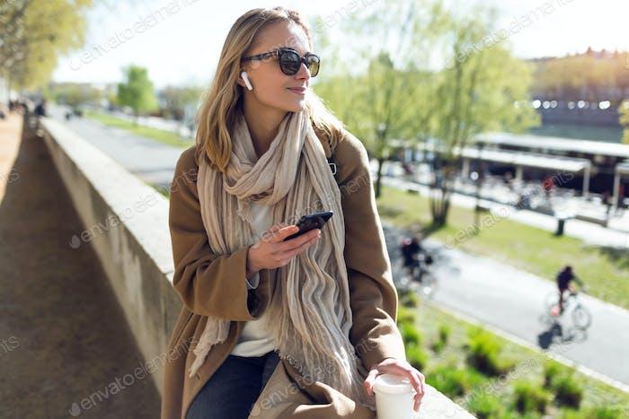 Hermosa mujer joven escuchando música con auriculares inalámbricos y