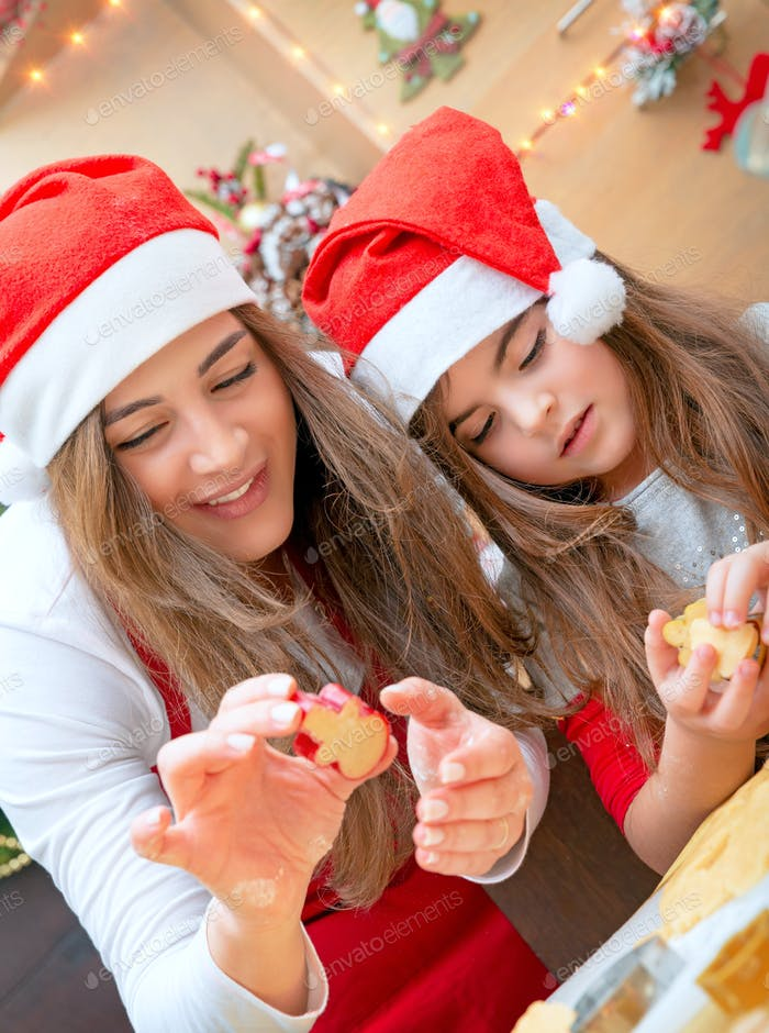 Mother and daughter doing Christmas sweets