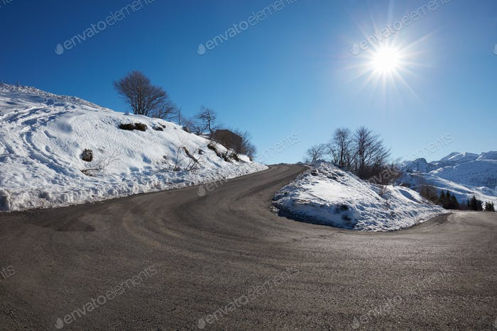 Empty mountain road curve on Alps with snow on sides, blue sky i