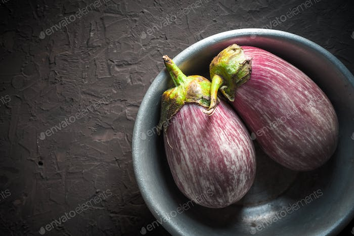 Colored eggplants in a metal bowl on a beige background