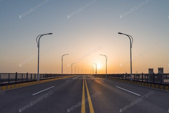 road on bridge in sunrise