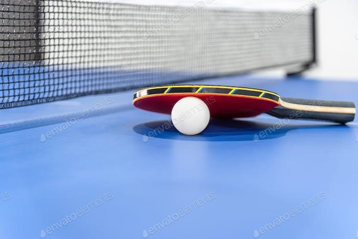 Nahaufnahme rote Tischtennis-Paddel weiße Kugel und ein Netz