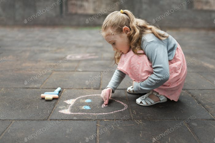 girl in a pink dress drawing chalk on  pavement
