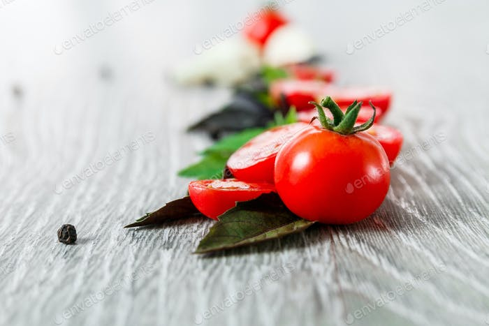 Close up of cherry tomatoes, garlic and fresh basil on grey wooden  background. Frame. Copy space.
