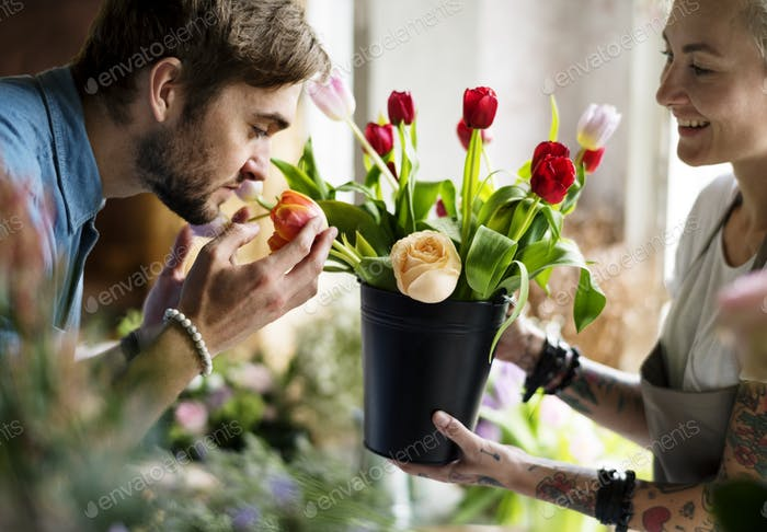 Man Smelling Fresh Flowers in Pot