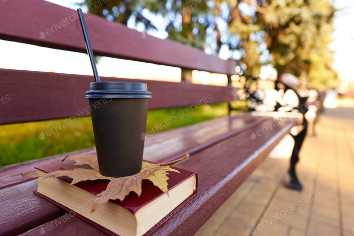 Cup of coffee and book in autumn park