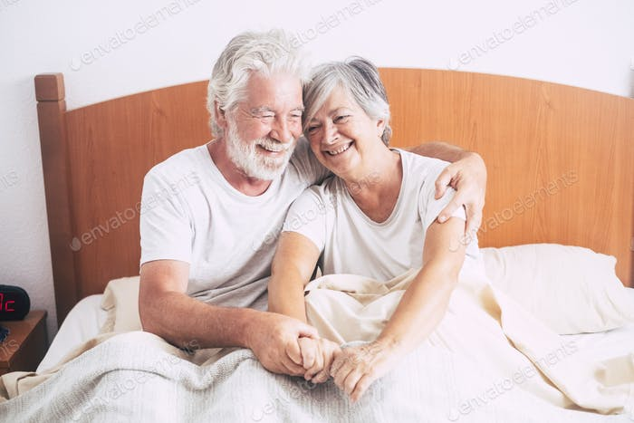 beautiful couple of mature and retired seniors sitting together on the bed at the bedroom