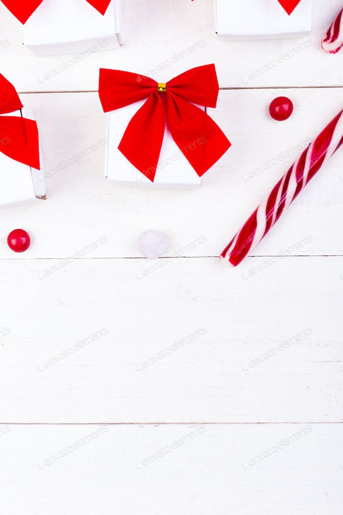 Christmas gifts, white little boxes with red bow  and candies on white wooden background. Flat la