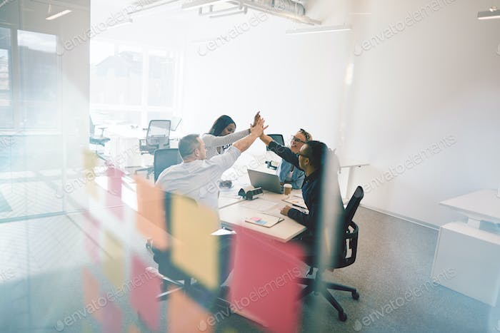 Diverse coworkers high fiving together during an office meeting