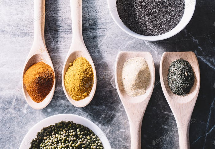 Spices on spoons, chia seeds and green beans in bowls.