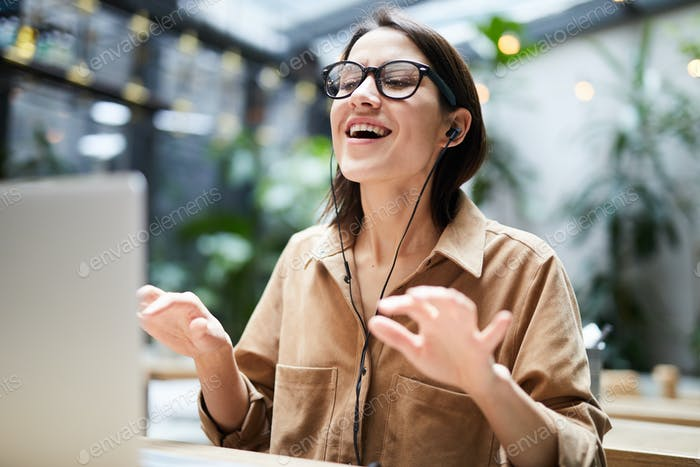 Young woman singing favorite song at workplace