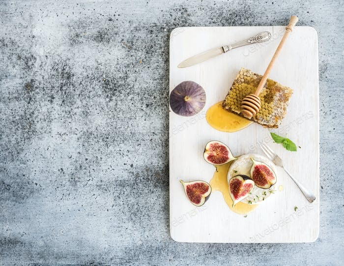 Camembert or brie cheese with fresh figs, honeycomb and glass of white wine on serving board