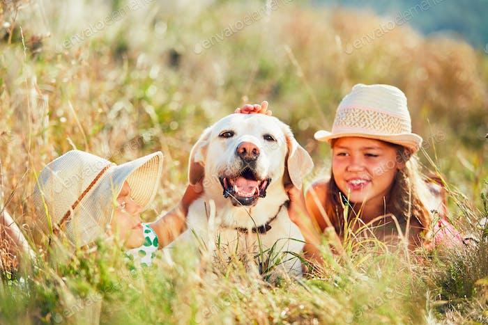 Die beiden Mädchen umarmen den Hund