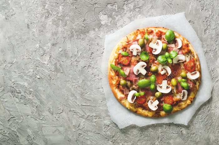 Fresh italian pizza with mushrooms, ham, tomatoes, cheese on on backing paper, grey concrete