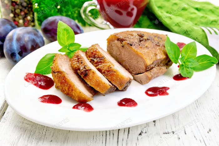 Duck breast with plum sauce and basil in plate on board