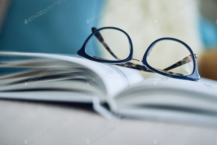 Soft focus glasses, book on the sofa. Abstract book blur background.
