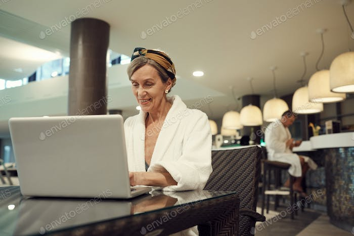Senior Woman Using Laptop in SPA