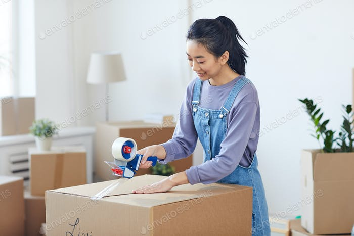 Asian Woman Packing Boxes for Moving Out