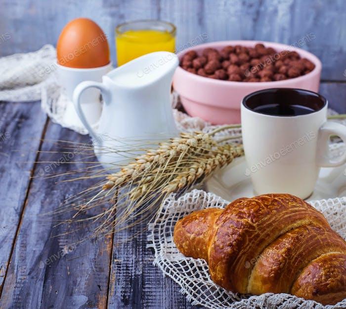 Croissant, cereal flake, coffee, milk, orange juice, boiled egg for breakfast