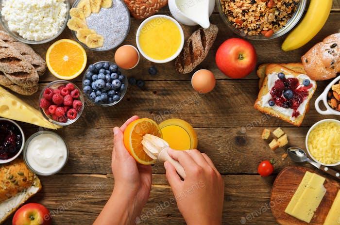 Woman squeezing orange fruit and making juice. Girl cooking breakfast. Healthy breakfast ingredients