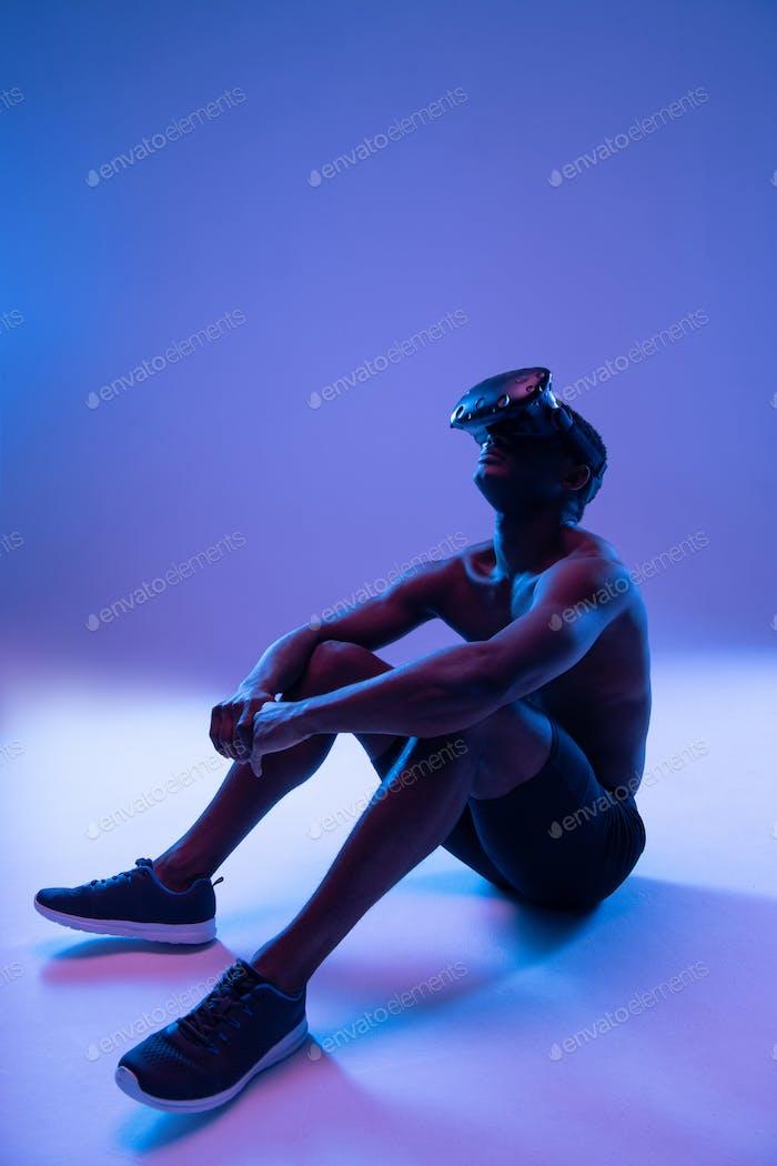 Dreamy ethnic sportsman exploring virtual reality