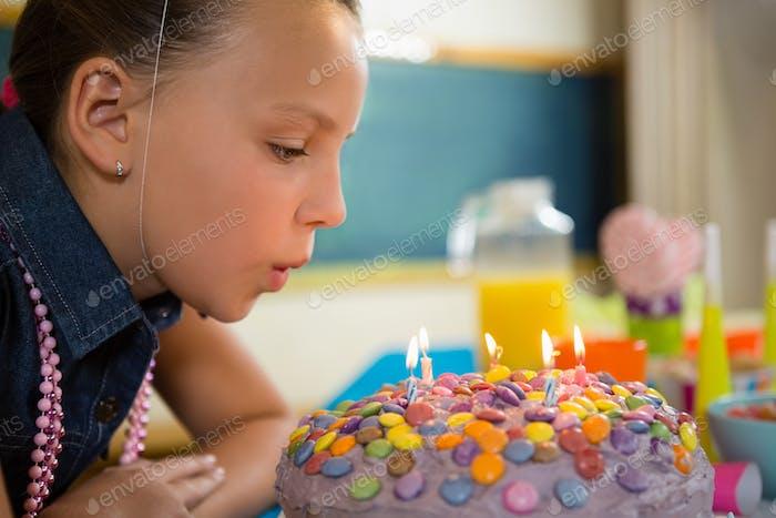 Mädchen bläst die Kerzen auf einem Geburtstagskuchen aus