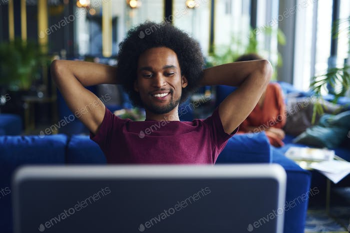 Satisfied African man relaxing in the office