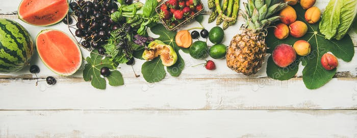 Seasonal fruit, vegetables and greens over wooden background, wide composition