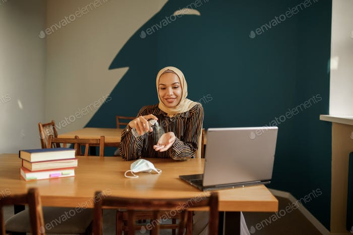 Arab female student in hijab disinfects hands