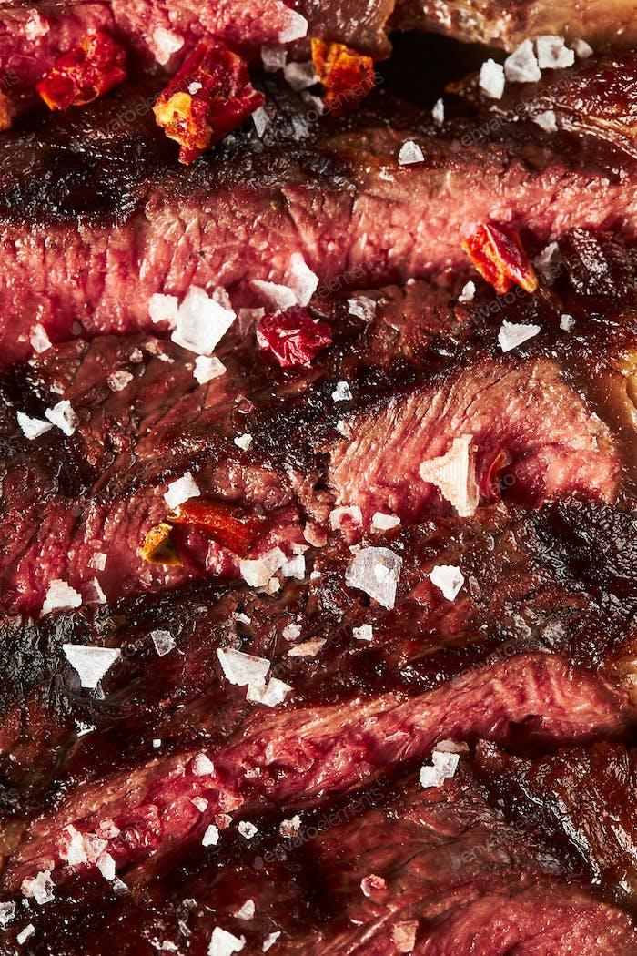 Close up of grilled Medium Rare Ribeye steak with salt cristals