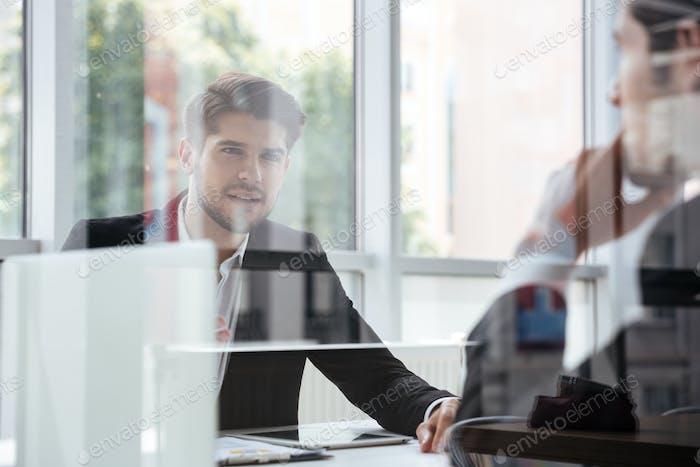 Dos jóvenes empresarios atractivos hablando de reunión Negocios en la oficina
