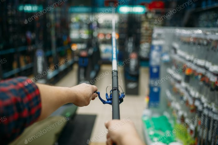 Angler with rod in fishing shop, first-person view