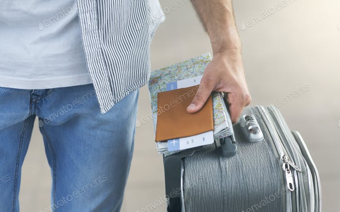 Man going to flight with suitcase, passport and airline ticket